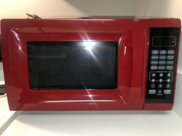 A mainstay red microwave oven sitting on a countertop