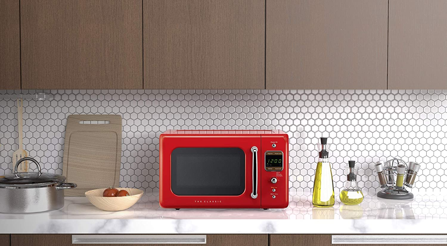 A red Microwave oven sitting a white countertop in a kitchen.