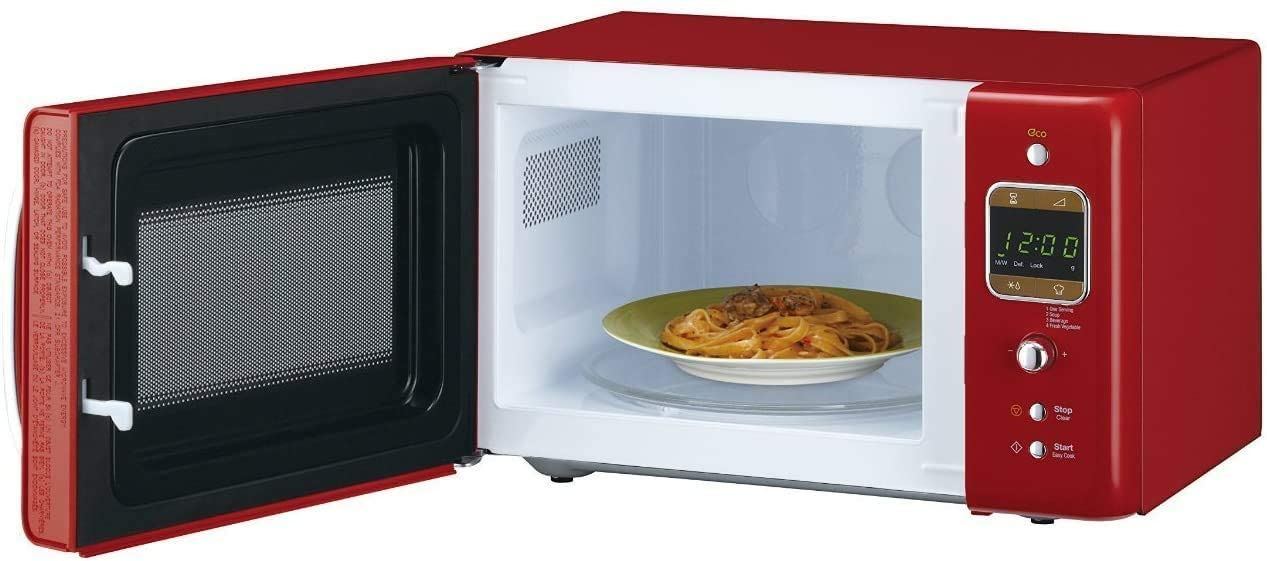 A red microwave oven with its door open showing a plate of pasta inside.